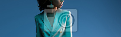 Sticker  panoramic shot of african american woman in suit isolated on blue