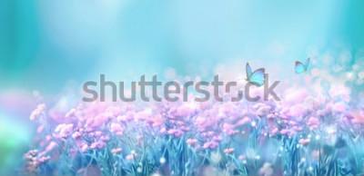Sticker Paysage naturel de printemps fleuri avec des fleurs lilas roses sauvages sur Prairie et papillons flottant sur fond de ciel bleu. Image artistique aérienne douce et rêveuse. Flou artistique, traitemen