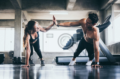 Sticker Personal trainer helping woman exercising in the sport gym