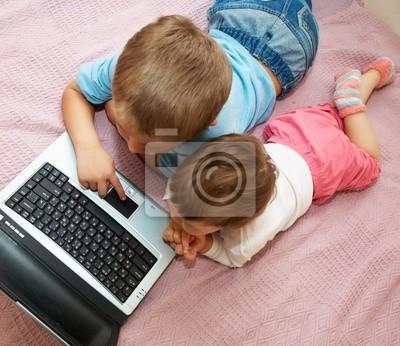 Petite fille et garçon assis en face d'un ordinateur portable