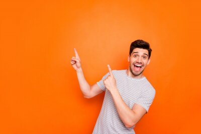 Sticker Photo of attractive guy hold hands fingers direct up empty space excited good mood sales person wear striped t-shirt isolated bright orange color background