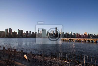 Pier et clôture à Gantry Plaza State Park et à Manhattan sous l'ombre