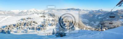 Sticker Piste de ski alpin panorama hivernal avec remontées mécaniques, skieurs et forêt enneigée.
