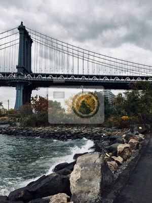 Pont de Manhattan et rochers au bord de la rivière avec ciel nuageux
