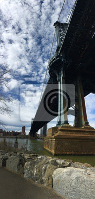 Pont de Manhattan sur la rivière et les roches au parc du pont de Brooklyn avec le ciel nuageux