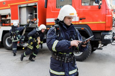 Sticker Portrait of firefighter in fire fighting operation, fireman in protective clothing and helmet using tablet computer in action fighting.