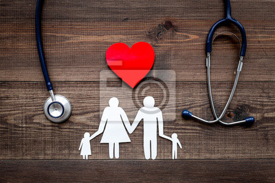 Sticker Prenez une assurance santé pour la famille. Stéthoscope, coeur de papier et silhouette de famille sur la vue de dessus de fond en bois