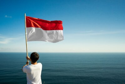 Sticker proud indonesian man on a beach cliff raising red and white indonesia flag