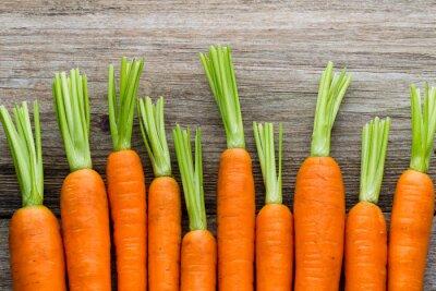 Sticker Rameau de carottes fraîches sur fond de bois rustique.
