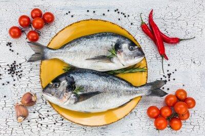 Sticker Raw dorado poisson frais sur la plaque jaune et les légumes sur table blanche. Vue de dessus.