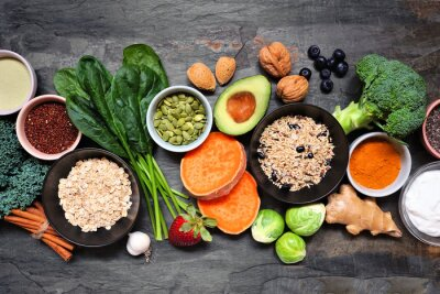 Sticker Selection of healthy food ingredients. Overhead view table scene on a dark slate background. Super food concept with green vegetables, berries, whole grains, seeds, spices and nutritious items.