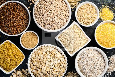 Sticker Selection of whole grains in white bowls - rice, oats, buckwheat, bulgur, porridge, barley, quinoa, amaranth on dark background