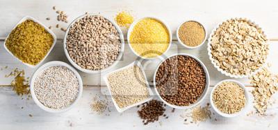 Sticker Selection of whole grains in white bowls - rice, oats, buckwheat, bulgur, porridge, barley, quinoa, amaranth, on white wood background