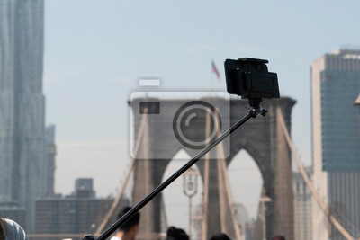 Selfie with smartphone and tripod on Brooklyn bridge on sunny day