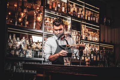 Sticker Serious barman is prepairing drinks for customers at posh bar.