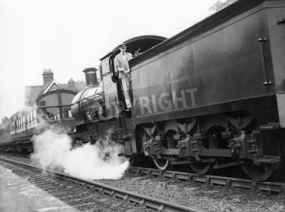 Sticker Sheffield Park, England - circa 1972 - A steam locomotive pulls a passenger train into Sheffield Park station on the preserved Bluebell Line Railway.