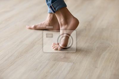 Sticker Side closeup view woman feet stands on warm wooden floor