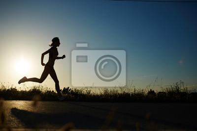 Sticker Silhouette de jeune fille athlétique courir sur la route à un coucher de soleil