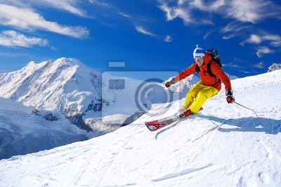 Sticker Skieur alpin descente dans les hautes montagnes contre le ciel bleu