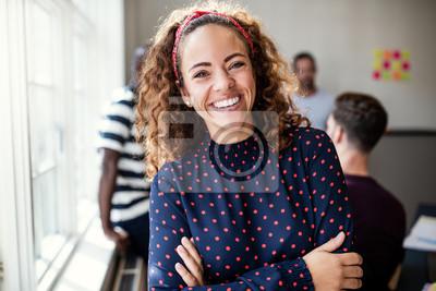 Sticker Sourire designer femelle debout dans un bureau moderne