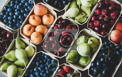 Sticker Summer fruit and berry variety. Flat-lay of ripe strawberries, cherries, grapes, blueberries, pears, apricots, figs in wooden eco-friendly boxes over grey background, top view. Local farmers produce