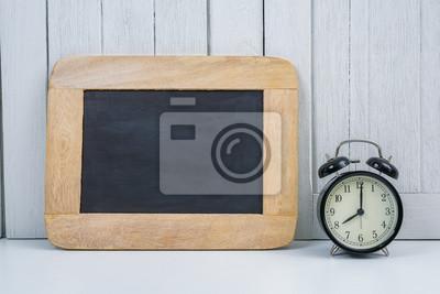 Tableau noir et réveil sur fond blanc en bois bureau bureau blanc