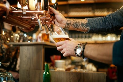 Sticker Tattooed caucasian barman pouring beer while standing in pub. Selective focus on hand.