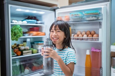 Sticker thirsty happy young asian girl open fridge door drinking a bottle of water