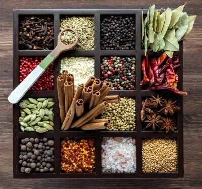 Sticker Top down view of a variety of whole spices in a compartment box with a wooden spoon of fennel seeds on top.