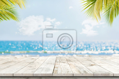 Sticker Top of wood table with seascape and palm leaves, blur bokeh light of calm sea and sky at tropical beach background. Empty ready for your product display montage.  summer vacation background concept.