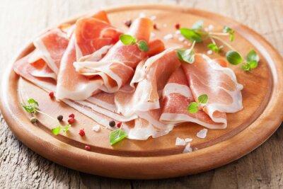 Sticker tranches de jambon prosciutto sur planche à découper avec de l'origan et le poivre