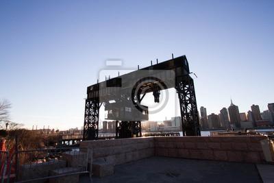 Transférer les ponts, les pignons de soutien et les piles au parc d'état de Gantry Plaza en silhouette avant le coucher du soleil