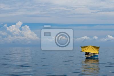 Un bateau de pêcheur jaune dans les eaux tropicales turquoise