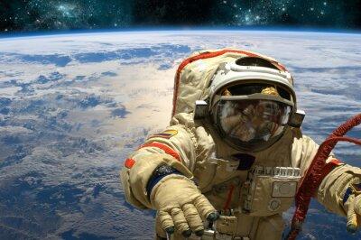 Sticker Un cosmonaute flotte dans l'espace. - Éléments de cette image fournis par la NASA.
