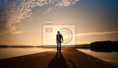 Un homme va sur la jetée de béton au lever du soleil