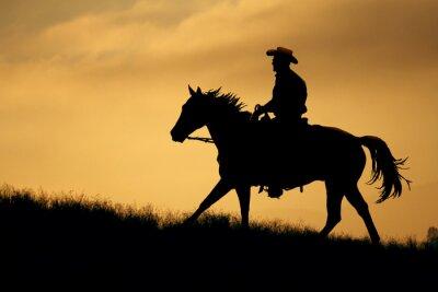 Sticker Une silhouette d'un cow-boy et le cheval marchant jusqu'à une prairie avec un fond de ciel orange et jaune.