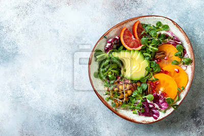 Sticker Vegan, detox Buddha bowl with turmeric roasted  chickpeas, greens, avocado, persimmon, blood orange, nuts and pomegranate. Top view, flat lay, copy space