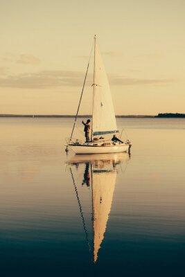 Sticker Voilier sur un lac calme avec le reflet dans l'eau. Paysage de scène sereine.