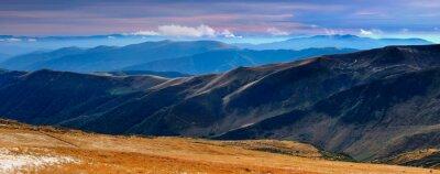 Sticker Vue panoramique sur les montagnes d'automne et les sommets recouverts de la première neige au coucher du soleil.