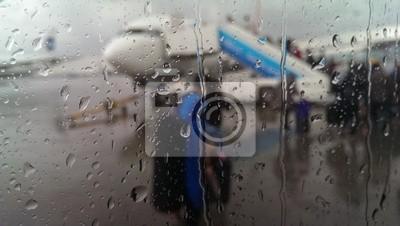 Vue sur l'aéroport pluies de fenêtre avec des gouttes