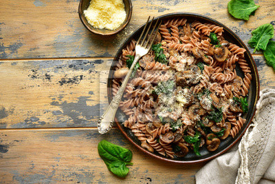 Sticker Whole wheat fusilli pasta with mushroom and spinach.Top view with copy space.