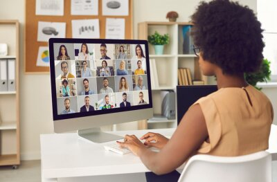 Sticker Woman having online business conference or video call staff meeting. Young black lady sitting at office desk with computer talking to team of coworkers who work from home or have hybrid work schedule