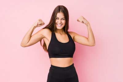 Sticker Young caucasian fitness woman doing sport isolated showing strength gesture with arms, symbol of feminine power