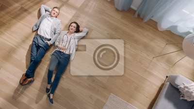 Sticker Young Couple are Lying on a Wooden Flooring in an Apartment. They are Happy, Smile and Laugh. Cozy Living Room with Modern Interior, Grey Sofa and Wooden Parquet. Top View Camera Shot.