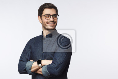 Sticker Young handsome business man dressed in casual denim shirt with smartwatch on wrist, isolated on gray background
