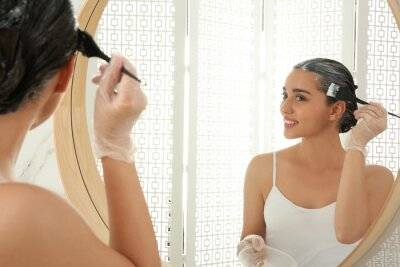 Sticker Young woman applying dye on hairs near mirror indoors