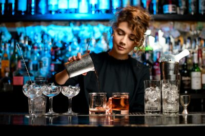 Sticker Young woman barman preparing cocktail and pouring it into glass.