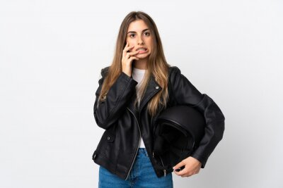 Sticker Young Woman holding a motorcycle helmet over isolated white background nervous and scared