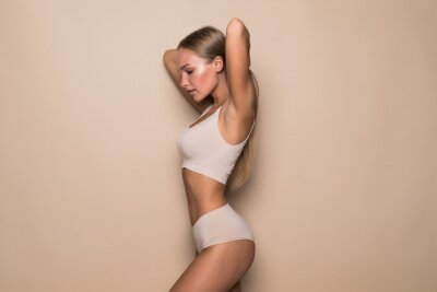 Sticker Young woman in beige underwear on beige background. Fitness, diet, skin and body care