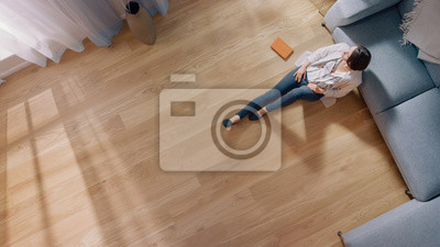 Sticker Young Woman is Sitting on a Floor and Looking out of the Window after Reading a Book. Cozy Living Room with Modern Interior, Grey Sofa and Wooden Flooring. Top View Camera Shot.